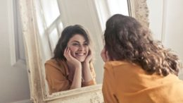 "A woman looking in the mirror wondering, ""How can personal development help me?"""